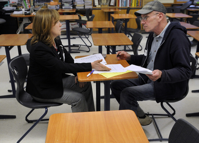 Marci Alexander, left, encourages Denis Thoet to send a letter to legislators for public access to an opiate antidote during the workshop sessions of the opiate symposium at Cony High School in Augusta on Wednesday.