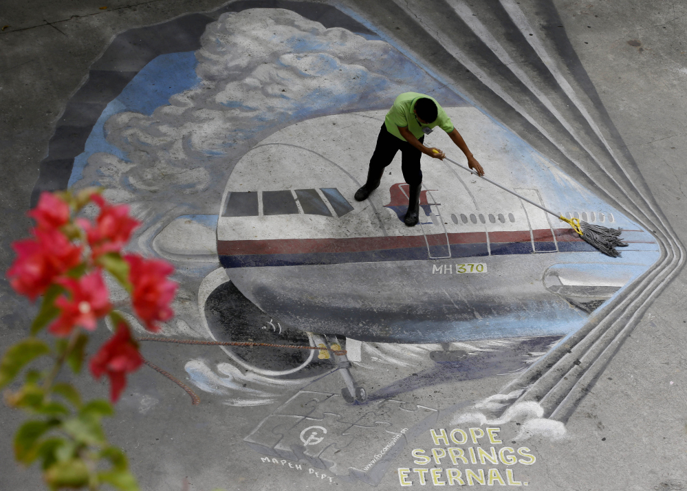 "2014 Associated Press File Photo A school utility worker mops a mural depicting the missing Malaysia Airlines Flight 370 at the Benigno ""Ninoy"" Aquino High School campus at Makati city east of Manila, Philippines."