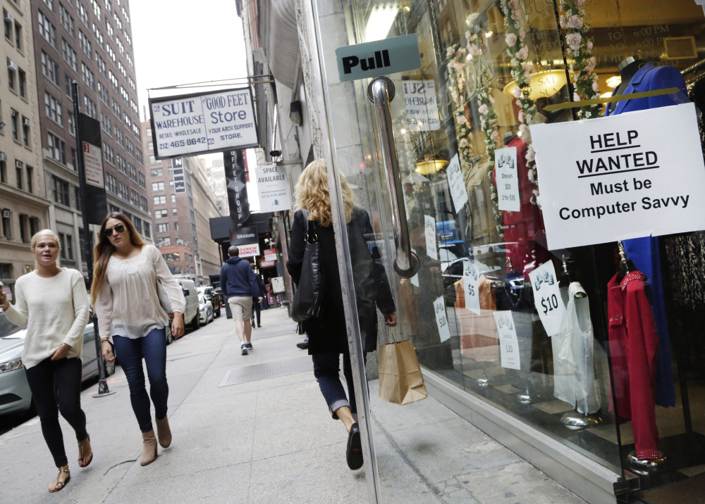 """A """"Help Wanted"""" sign hangs in a store window in New York in October. U.S. employers added 242,000 workers in February as retailers, restaurants and health care providers drove another solid month for the American job market. The Labor Department said the unemployment rate held steady at 4.9 percent."""
