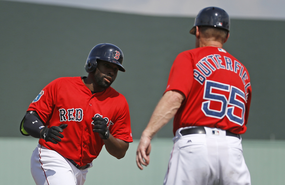 Jackie Bradley Jr. of the Boston Red Sox greets third-base coach Brian Butterfield while rounding the bases Friday after hitting a solo home run in the third inning of a 7-2 victory against the Tampa Bay Rays.