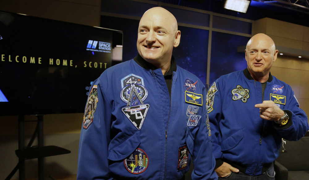 NASA astronaut Scott Kelly, left, and his twin, Mark, meet before a press conference Friday in Houston. They both took part in medical studies during Scott Kelly's flight.