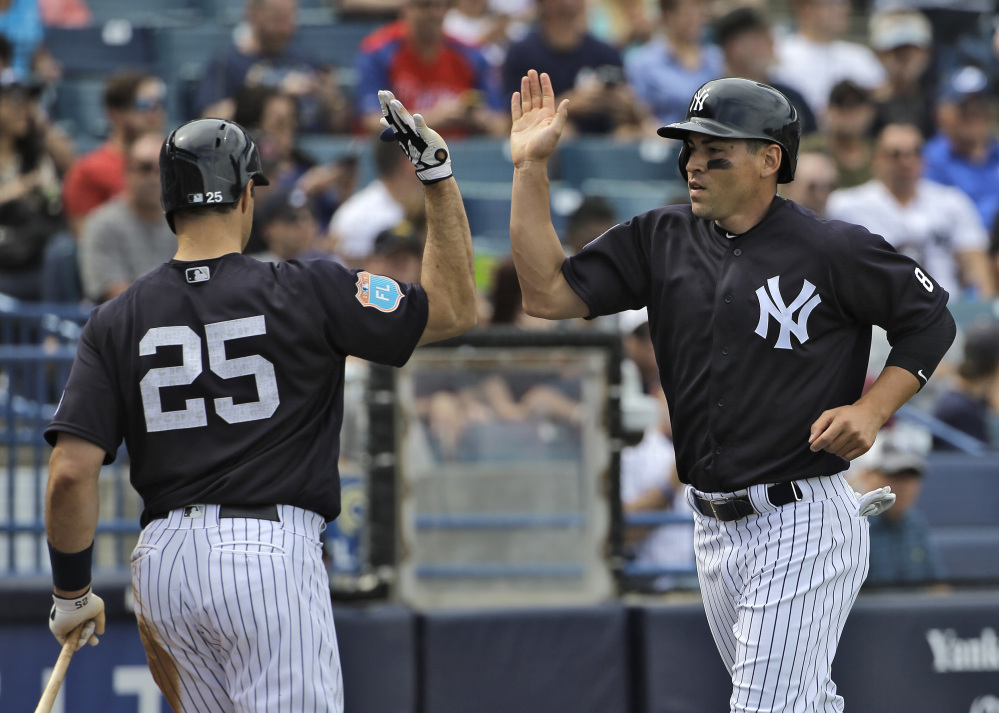 Jacoby Ellsbury, right, of the Yankees high fives on-deck batter Mark Teixeira after scoring on a ground out by Carlos Beltran off Boston Red Sox relief pitcher Robbie Ross Jr. during the fifth inning of a spring training game Saturday. The Yankees went on to win, 6-4.