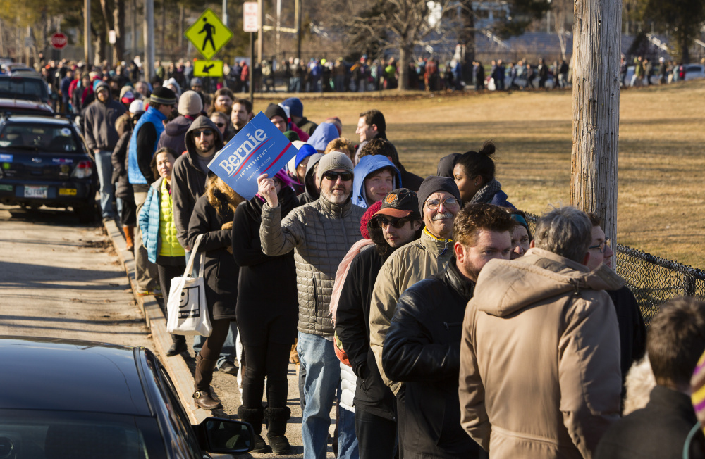 Voters wait in line to take part in the Democratic caucus at Deering High School in Portland on Sunday.   Carl D. Walsh/Staff Photographer