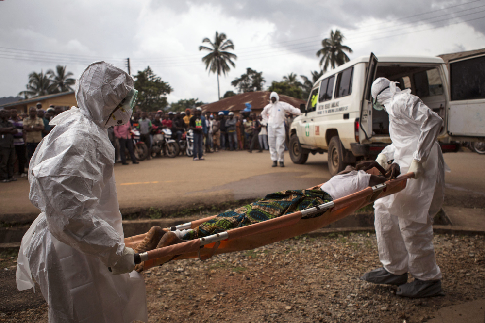 In this Sept. 24, 2014, file photo, healthcare workers load a man suspected of suffering from the Ebola virus onto an ambulance in Kenema, Sierra Leone.
