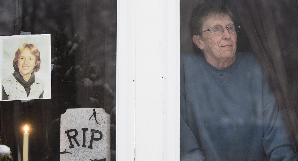 Pam McLain looks out the front porch window of her home in East Millinocket, where a candle has been burning for her murdered daughter, Joyce, since 1980. Kevin Bennett
