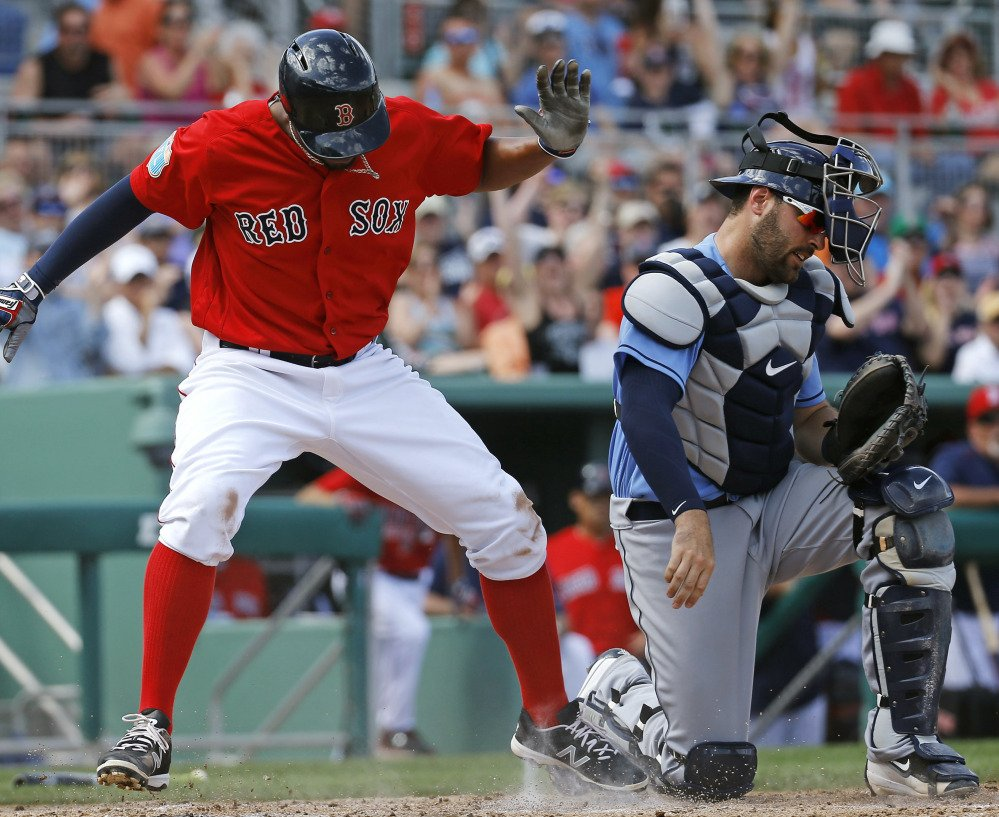 Xander Bogaerts of the Boston Red Sox slips past Tampa Bay catcher Curt Casali to score on a single by David Ortiz in the fourth inning of Tampa Bay's 3-2 victory Monday.