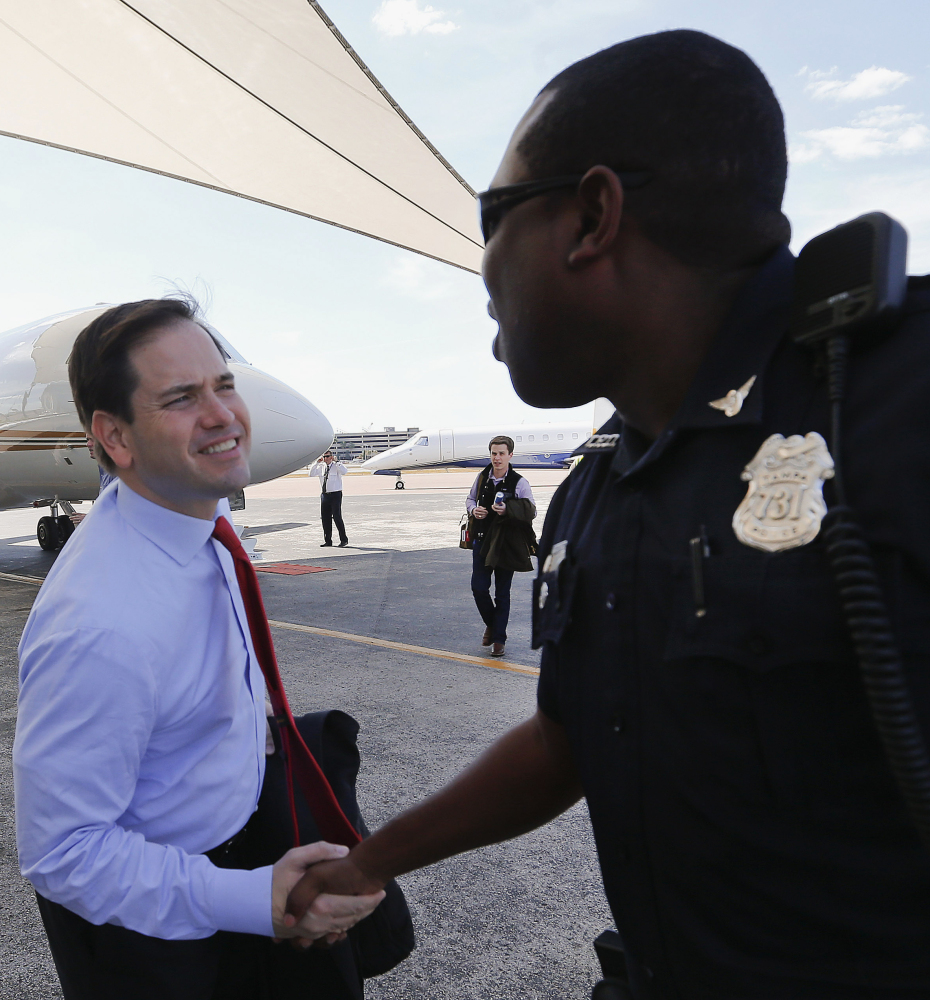 Sen. Marco Rubio shakes hands with a police officer in Tampa, Fla., Monday. That state's primary is next week.