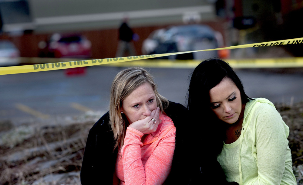 Amanda Padula, left, and Deborah Young on Sunday sit outside Altar Church in Coeur d'Alene, Idaho, where pastor Tim Remington was shot multiple times as he was leaving services earlier in the day. The two women said they benefited from Remington's Good Samaritan Rehabilitation program.