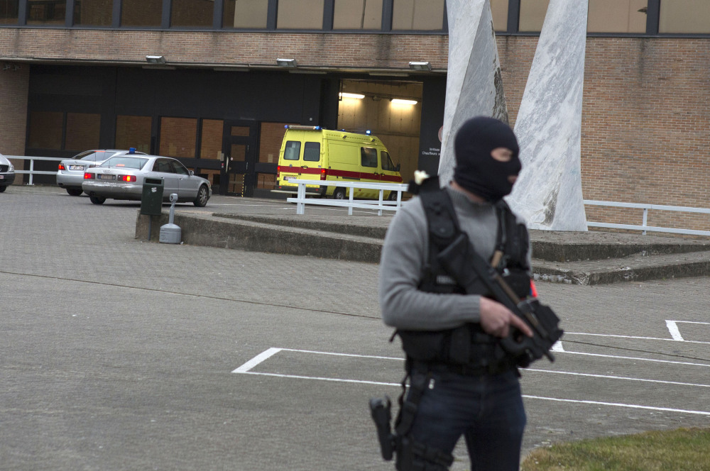 A special forces police officer stands guard as a police convoy and ambulance thought to be carrying captured fugitive Salah Abdeslam arrives at the federal penitentiary in Bruges, Belgium, on Saturday.