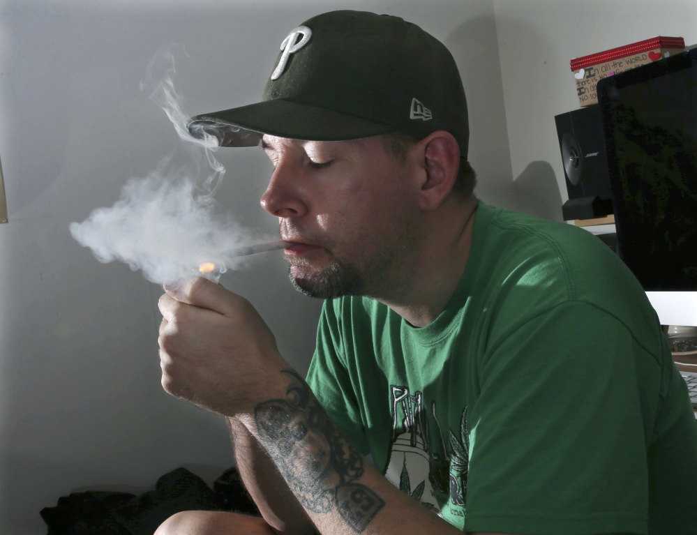 Former U.S. Marine Mike Whiter lights a marijuana cigarette before he starts editing a video project at his home in Philadelphia. A growing number of states are weighing whether to legalize marijuana to treat PTSD. While the research has been contradictory and limited, some former members of the military say marijuana helps them manage their anxiety, insomnia and nightmares.