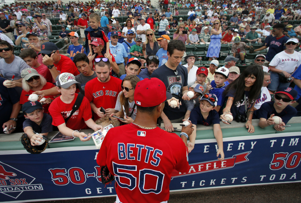 Mookie Betts takes a few minutes to sign autographs for fans before Thursday's spring training game against the New York Mets. The Red Sox won 4-1.