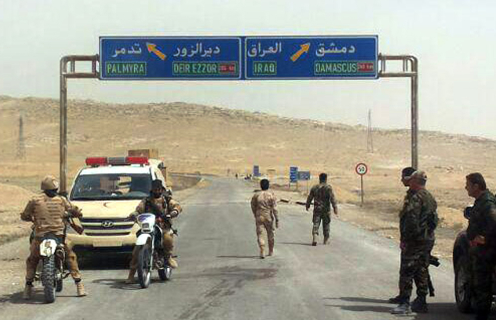 Syrian government soldiers gather near the Islamic State-held town of Palmyra Thursday, as government forces backed by Russian air power appeared close to storming the city.