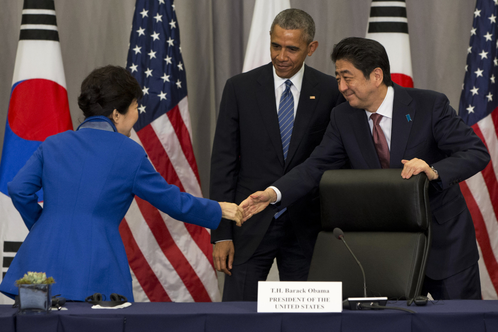 South Korean President Park Geun-hye, left, shakes hands with Japanese Prime Minister Shinzo Abe after they met with President Barack Obama at the Nuclear Security Summit in Washington on Thursday.