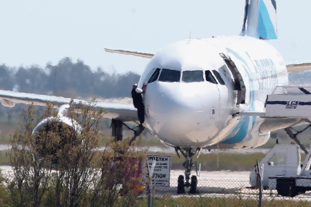 A man  leaves the hijacked aircraft of Egyptair from pilot window at Larnaca airport in Cyprus Tuesday. The Associated Press