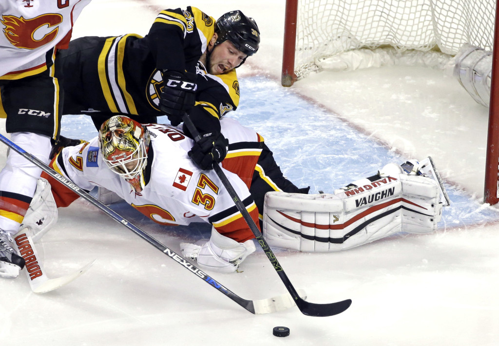 Bruins left winger Matt Beleskey reaches over Calgary goalie Joni Ortio during the first period Tuesday.   The Associated Press
