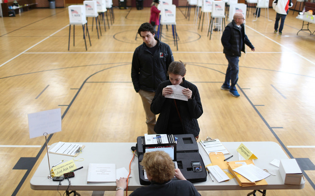 Voters in Highland Park, Ill., pick up ballots during the primary election in March.