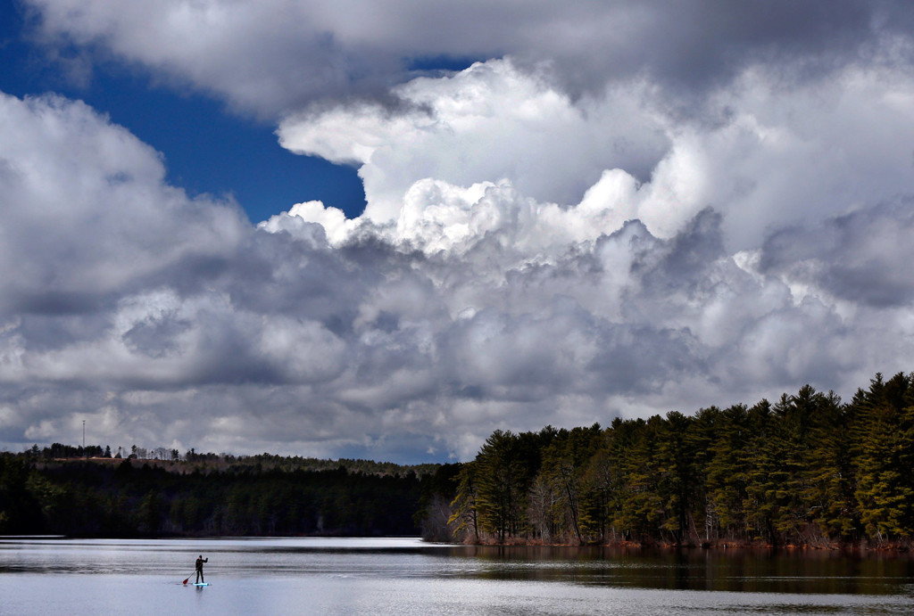 Storm clouds build before a thunderstorm as Jeff Warren of Auburn heads for shore on his paddleboard on Lower Range Pond on Thursday in Poland. Plenty of rain has offset the lack of snowmelt this spring in the Northeast.