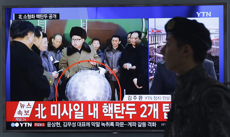 """A South Korean army soldier walks by a TV screen showing North Korean leader Kim Jong Un with superimposed letters that read: """"North Korea's nuclear warhead"""" during a news program at Seoul Railway Station in  South Korea."""