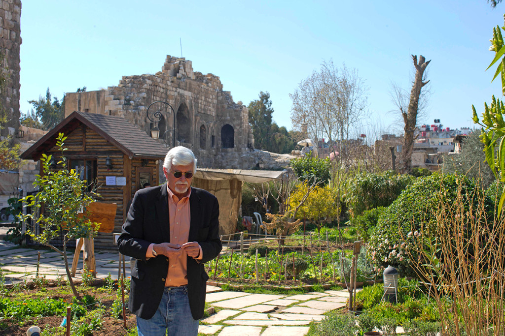 Thomas Webber walks in a garden next to the Citadel of Damascus, Syria. Webber, an American who was born and raised in Orchard Park, New York, has a part-time job in the English department of a local high school, where he shares his love of Charles Dickens with teenagers several times a week. The Associated Press