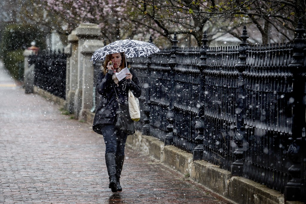 Meghan Donovan of Portland tries to stay dry from a spring snow flurry as she walks downtown from Munjoy Hill on Congress Street Tuesday morning. Gabe Souza/Staff Photographer