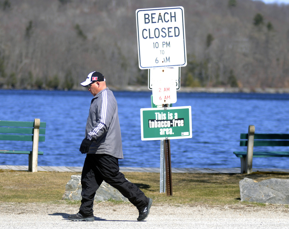 Chris Kempton walks past Winthrop's town beach Tuesday, a day after the Winthrop Town Council approved banning the use of e-cigarettes at the beach.