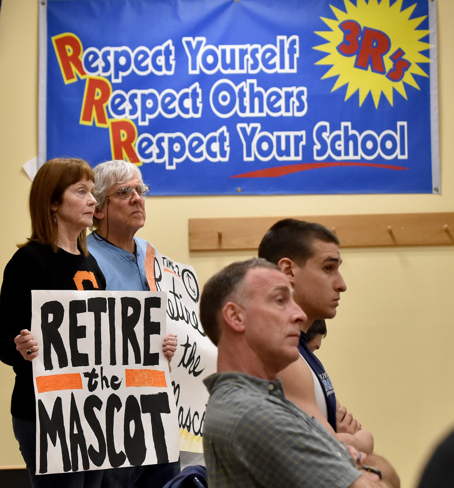 Linda Savage, back left, and Mark Roman, back center, stand with signs calling for the Skowhegan Area High School Indian mascot be retired during a Skowhegan school board meeting at Skowhegan Middle School on Thursday night.