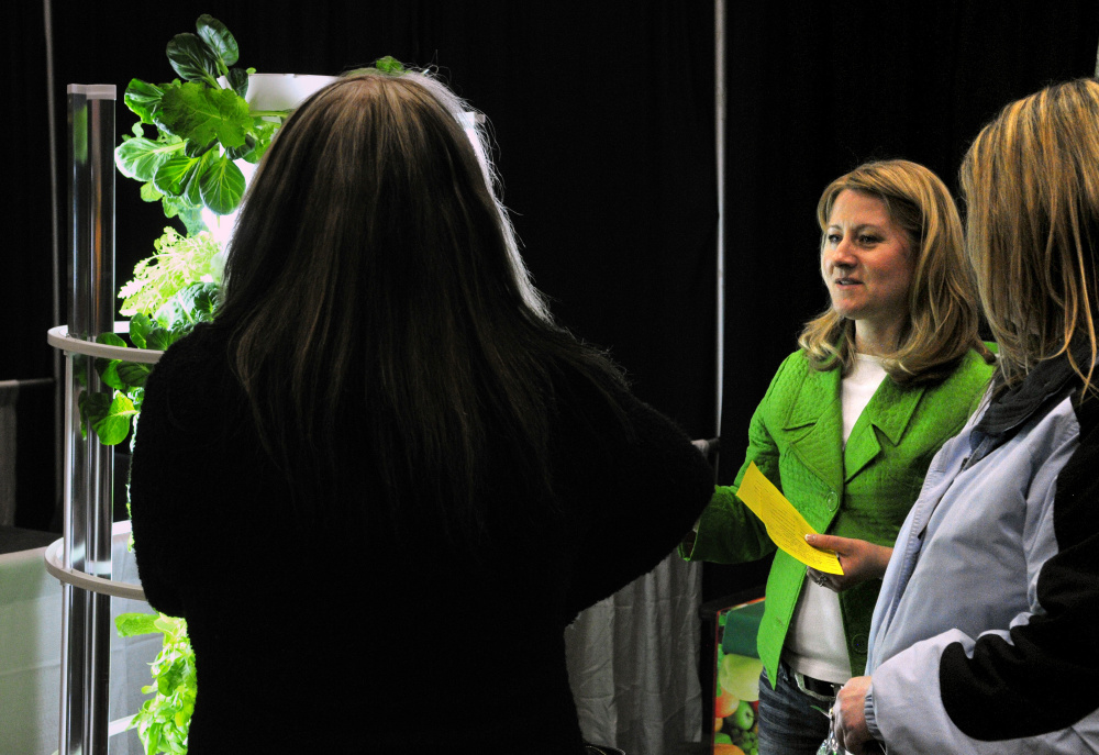 Natalia Irving, center, talks to customers about a tower garden Friday during the 43rd annual Manchester Lions Club Home and Garden Show at the Augusta Civic Center.