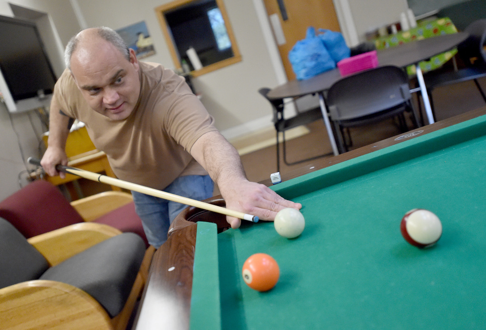 Andrew Zelonis plays a game of pool after helping with the taco dinner clean-up at the Waterville Social Club on Ticonic Street on Friday. The club faces new state-imposed requirements that officials fear could exclude some club members.