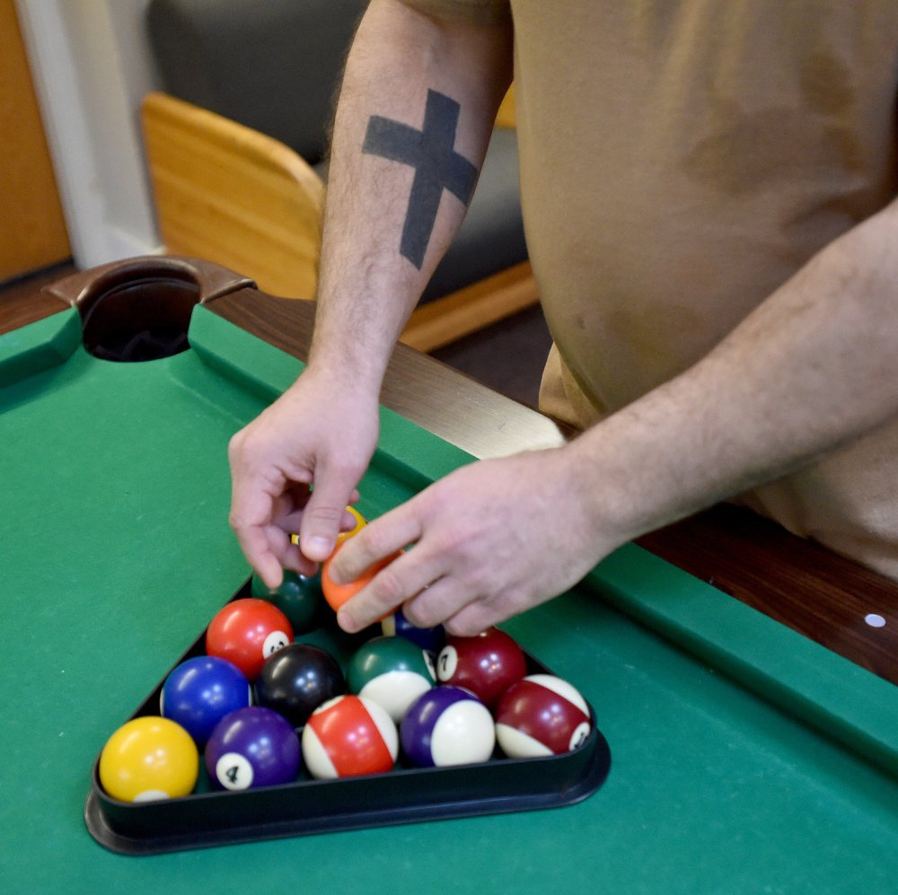 "Andrew Zelonis racks the balls for a game of billiards during an evening at the Waterville Social Club on Ticonic Street on Friday. Zelonis said he appreciates the time he spends at the Social Club. ""I've made friends and I can do my laundry,"" he said."