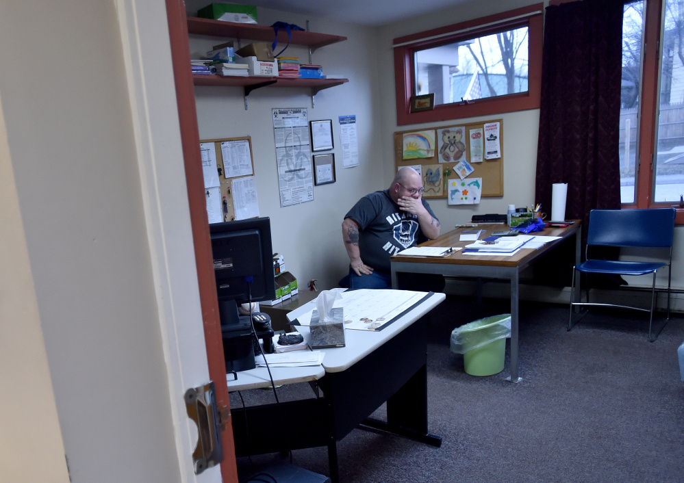 Myron Hutchins, a staff member at the Waterville Social Club on Ticonic Street, does the books at the end of the day on Friday. Hutchins is one of two staff members at the social club, which faces new state-imposed requirements that officials fear could exclude some club members.