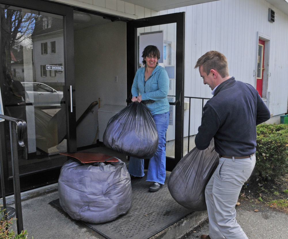 Sarah Miller, the Augusta Food Bank director, left, holds the door for Chris Lothridge, sales manager of the Hampton Inn in Augusta, as he carries in bags of linens for Addie's Attic on Friday at the St. Mark's Episcopal Church parish hall in Augusta. Several local hotels are collecting and donating linens and personal care products to Addie's Attic and the Every Day Basics Essentials Pantry that are operated in the building on Pleasant Street.