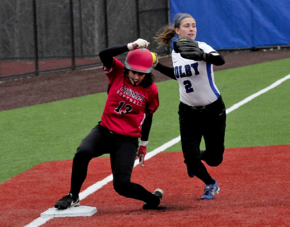 Colby College player Katie McLaughlin looks to throw to first after tagging out Thomas College runner Courtney Veilleux at third base during a game on Monday in Waterville.