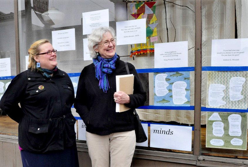 Serena Sanborn, left, and Nina Pleasants speak about the haiku poems and artwork on the front window of the former Variety Drug store in Skowhegan on Monday. The Wesserunsett Arts Council is sponsoring Japanese haiku poems all over Skowhegan as part of poetry month.