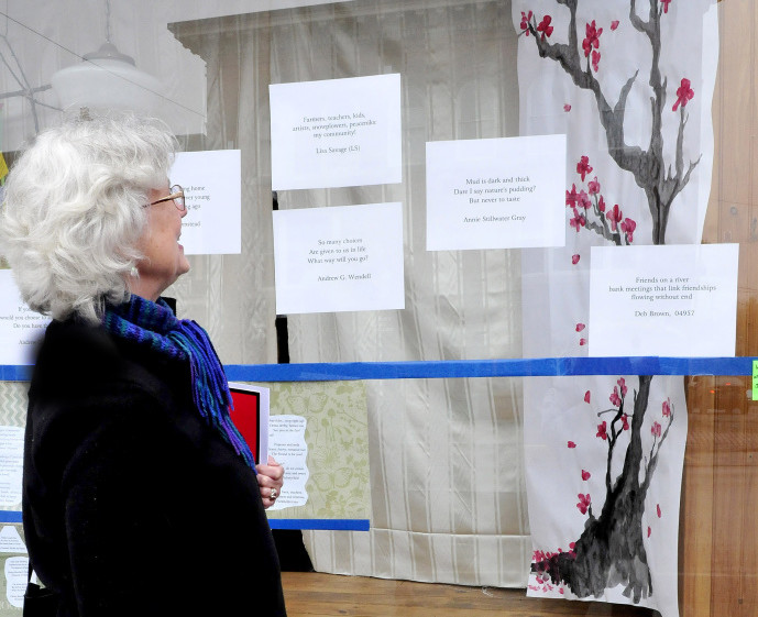Nina Pleasants admires haiku poetry and artwork in a Skowhegan downtown store front on Monday.