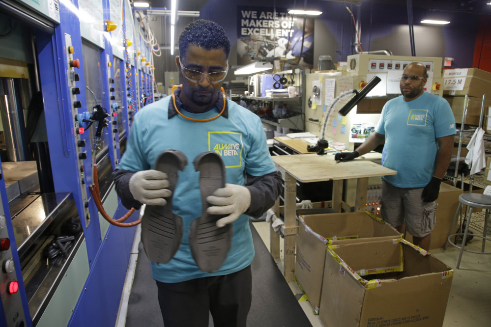 Joao Rodrigues, left, removes a pair of newly formed midsoles for the proposed New Balance 950v2 sneaker in July. The sneaker has passed military testing and would be used by the military. The company and Maine's congressional delegation are pressing the Department of Defense and the Obama administration to keep promises that the military will require personnel to use American-made athletic shoes.