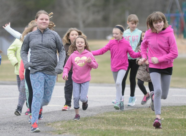 Gilbert Elementary School students run through Augusta after school Monday as part of Girls on the Run, a national program that promotes physical activity and positive youth development.
