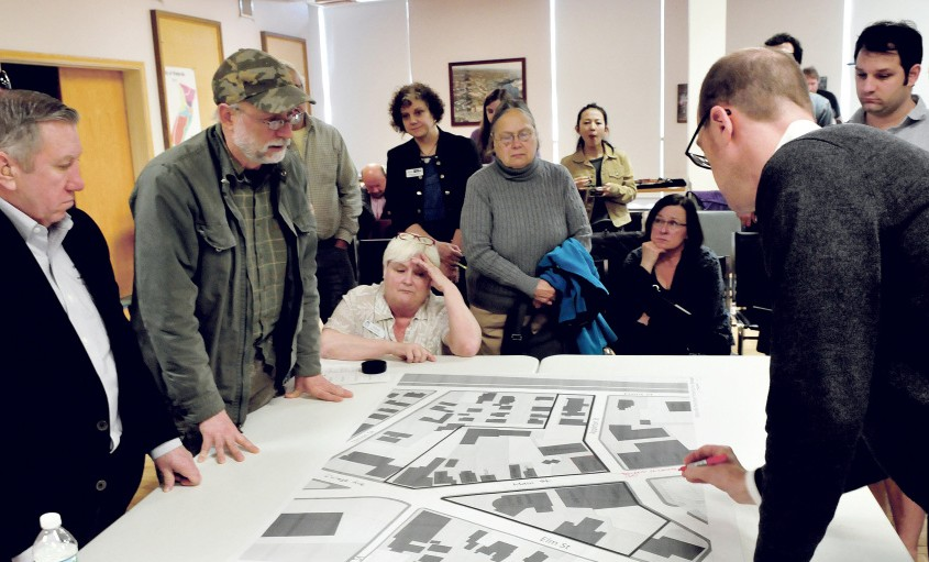 Bruce Fowler, wearing a cap, asks questions of planner Neil Kittredge, right, over a section map of downtown Waterville during a revitalization discussion Wednesday.