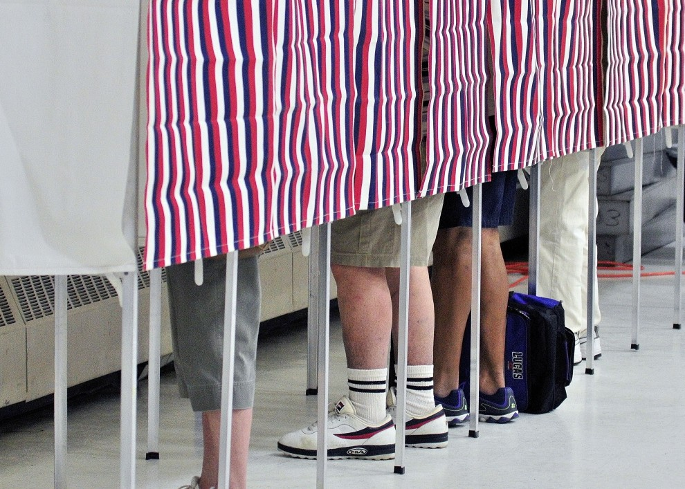 Four voters cast ballots June 10, 2014, in voting booths in the Augusta State Armory. The town of Monmouth is trying to decide whether to appoint town employees as election clerks.
