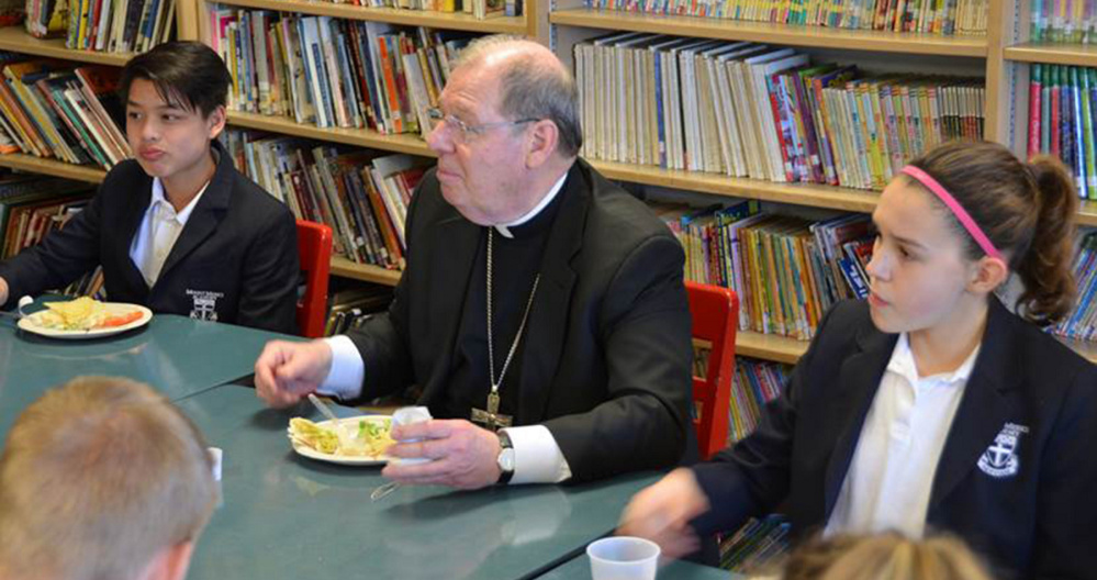 Bishop Robert P. Deeley ate lunch with the eighth graders during his April 13 visit to Mount Merici Academy in Waterville. From left are Yanic Boulet, Bishop Deeley and Lauren Bourque.