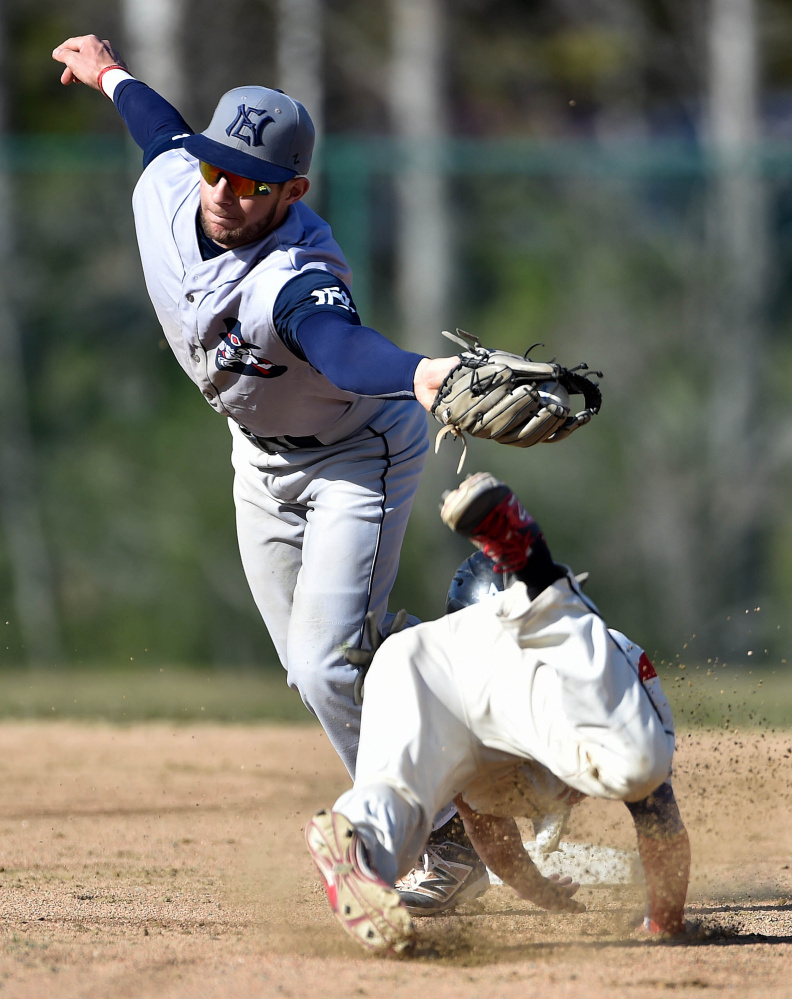 Thomas College's Tristan Pena dives safely under the tag from New England College's Tomas Pueyo (14) in the first inning of the second game of a doubleheader Saturday at Thomas College in Waterville.
