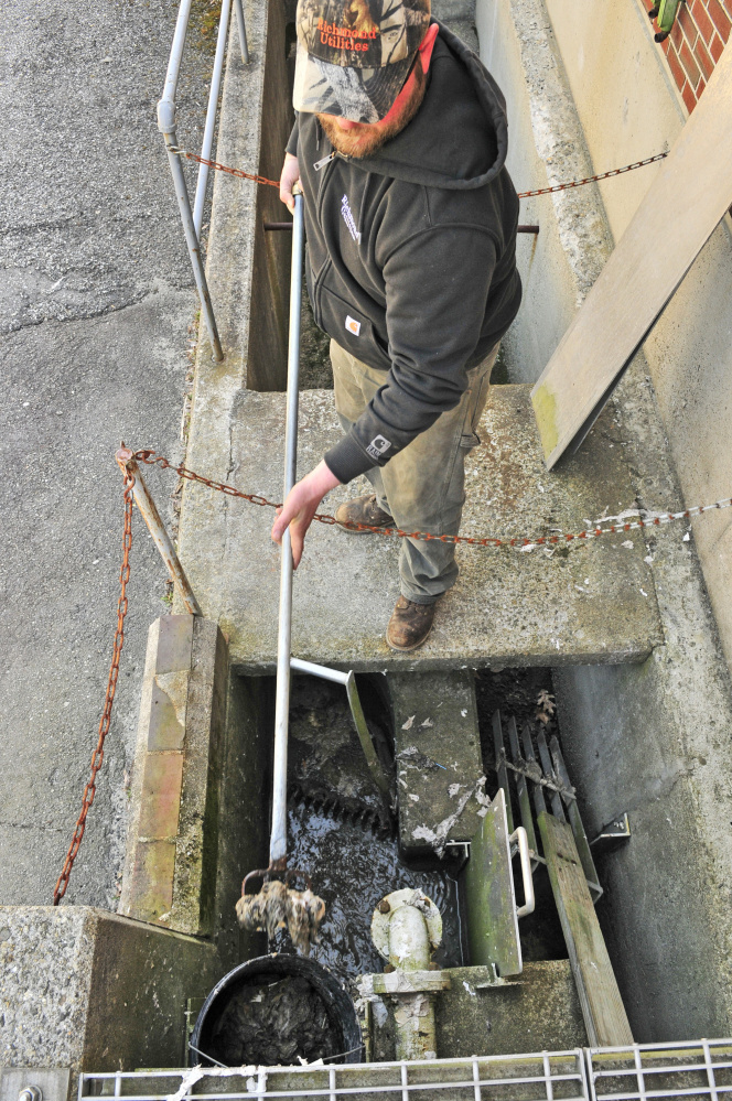 Operator Anthony Soucy rakes the bar rack on Friday at Richmond Utilities District sewage treatment plant.