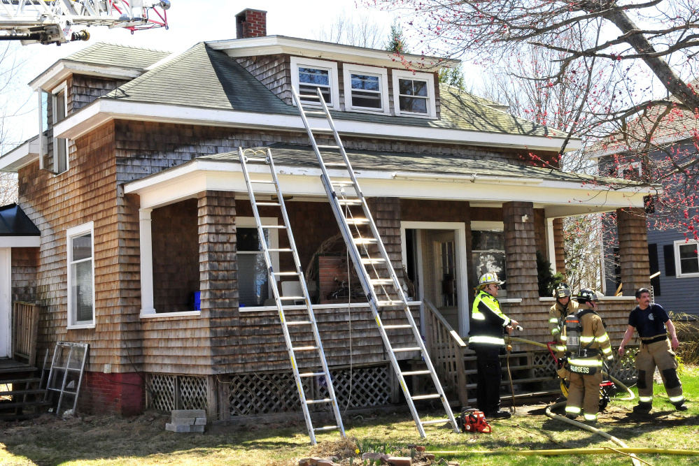 Waterville firefighters, including Chief Dave Lafountain, left, set up a fan Thursday to ventilate smoke from a home on Colonial Street in Waterville. Officials think an electrical problem in the attic caused the fire.