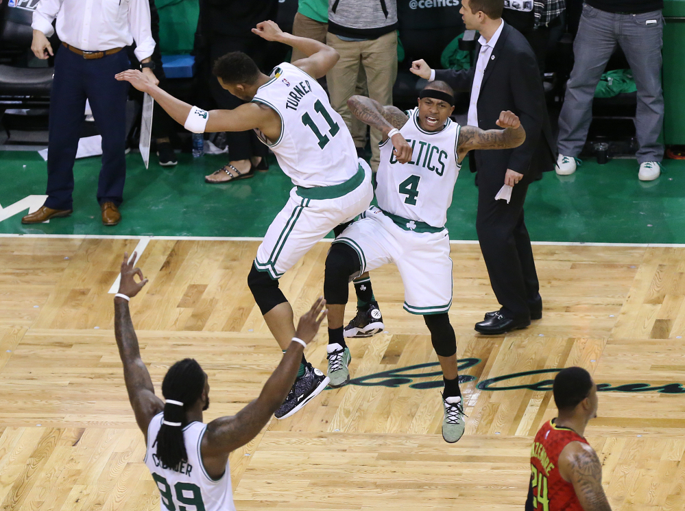 Atlanta's Kent Bazemore, lower right, walks off the court as the Boston's Isaiah Thomas (4) leaps to celebrate hitting his three pointer with teammate Evan Turner, while Jae Crowder, lower left, also celebrates in Game 4 of a first-round NBA playoff series Sunday in Boston .