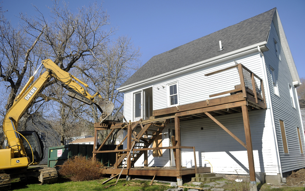 Adam Mealey rips off the deck of the house at 226 Water St. in Hallowell during demolition on Monday.