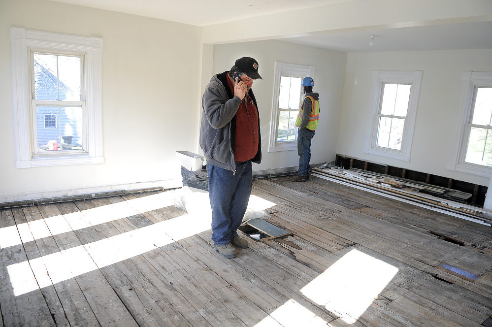 Jon Canty, left, and Adam Mealey inspect the second floor of the house at 226 Water St. in Hallowell on Monday.