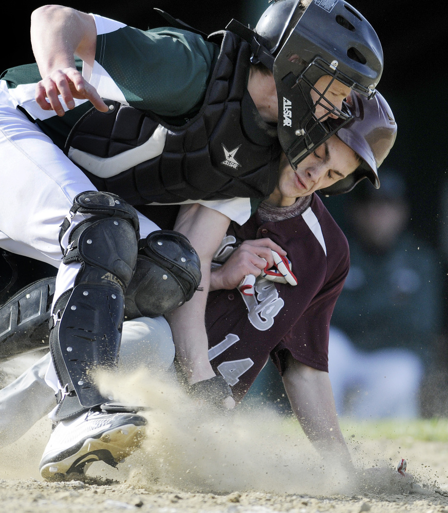 Monmouth Academy's Gage Cote slides safely into home under Winthrop catcher Matt Ingram during a Mountain Valley Conference game Monday afternoon in Winthrop.