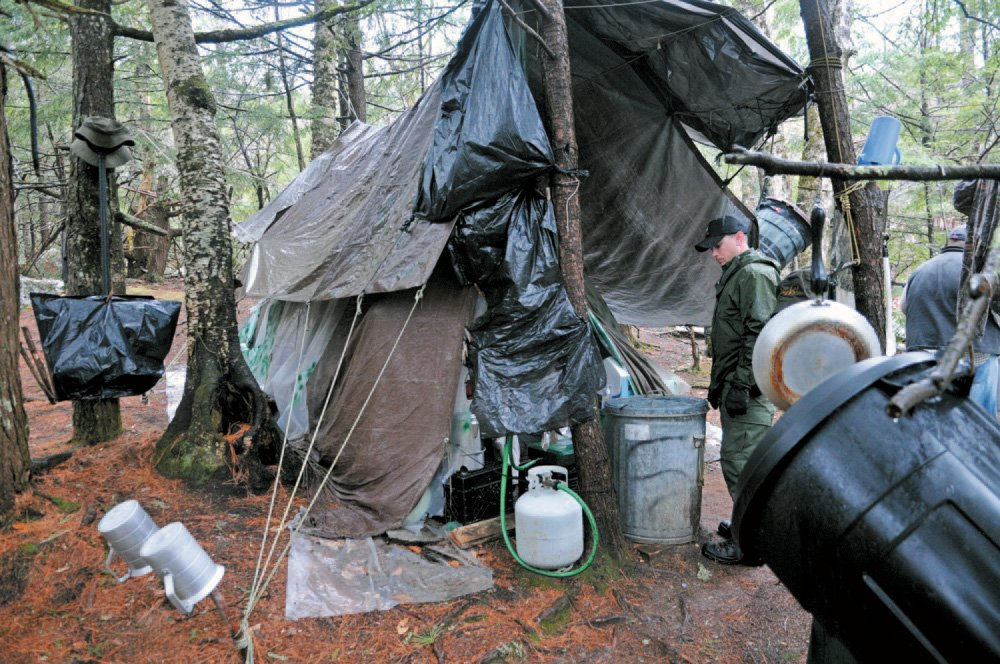 District Game Warden Aaron Cross inspects Christopher Knight's camp in a remote, wooded section of Rome in this file photo.