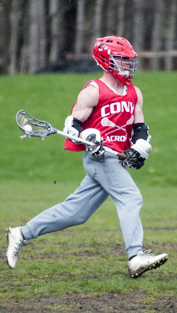 Bret Sproul runs with the ball during lacrosse practice Tuesday at Cony High School in Augusta.