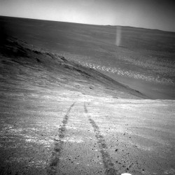 From its perch high on a ridge, the Mars rover Opportunity took this picture March 31 of a dust devil twisting through Mars' Marathon Valley below. The view looks back at the rover's tracks leading up the north-facing slope of Knudsen Ridge.