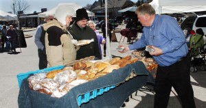 Karl Rau of Good Bread sets out his products as customers Jeannie and David Gubbins Jr. wait to buy breads at the Downtown Waterville Farmer's Market on Thursday. The market opened for the season and will be in The Concourse parking lot ever Thursday through Nov. 17.